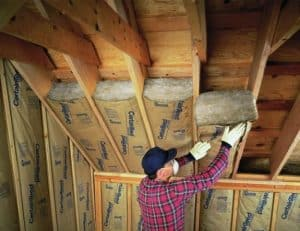 A tradesman insulating a roof with insulating materials.