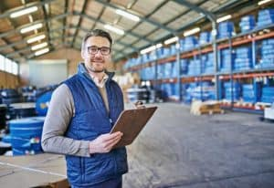 A man in a warehouse with a clipboard.